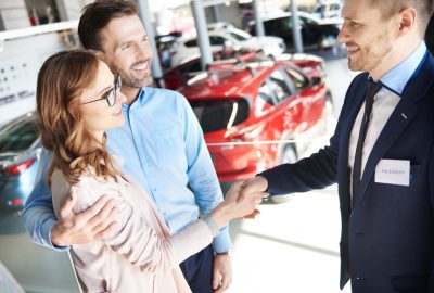Mid adult couple making a great deal with salesman